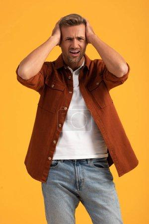 emotional man touching head isolated on orange