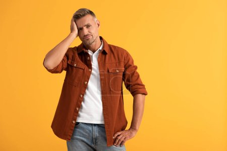 displeased man touching head and standing with hand on hip isolated on orange