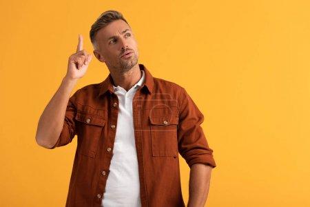 Photo pour Beau homme geste tout en ayant idée isolé sur orange - image libre de droit