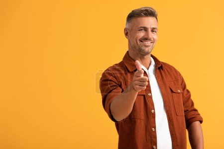 selective focus of cheerful man pointing with finger isolated on orange