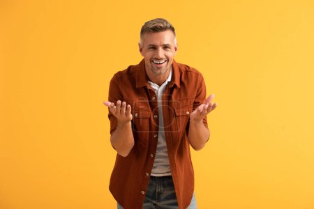 Foto de Hombre feliz mirando la cámara y gestando aislado en naranja - Imagen libre de derechos