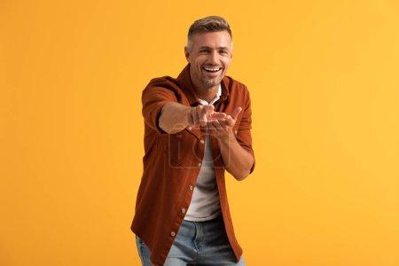 selektiver Fokus des glücklichen Mannes, der in die Kamera blickt und mit dem Finger auf orange zeigt