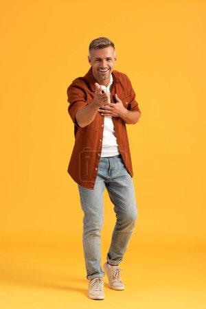 selektywny ostrość szczęśliwy człowiek patrząc w aparat i wskazując palcem na pomarańczowy