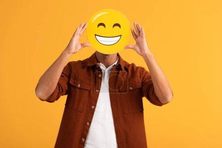 kyiv, ukraine - 24. September 2019: Mann bedeckt Gesicht mit glücklichem Emoticon isoliert auf Orange