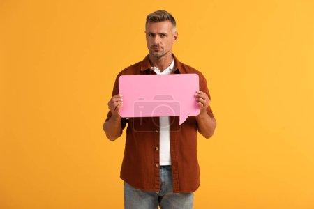 bel homme tenant bulle de parole rose isolé sur orange