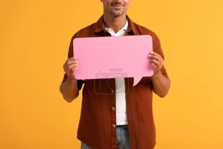 cropped view of happy man holding pink speech bubble isolated on orange