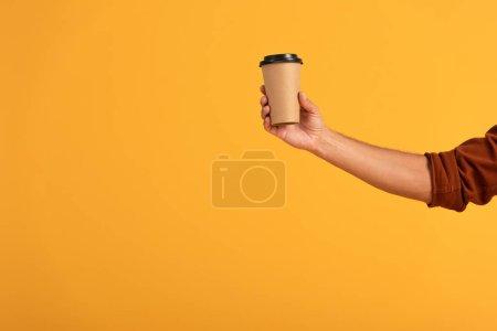 Photo pour Vue recadrée de l'homme tenant tasse en papier isolé sur orange - image libre de droit