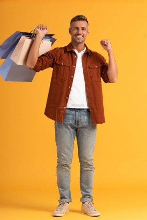 Photo pour Homme gai tenant des sacs à provisions colorés sur orange - image libre de droit