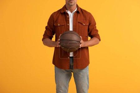 Photo pour Vue recadrée de l'homme tenant le basket isolé sur orange - image libre de droit