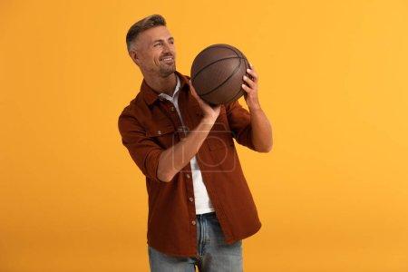 Photo pour Homme gai tenant basket isolé sur orange - image libre de droit