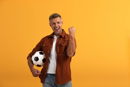 Photo for Happy man standing with football and celebrating isolated on orange - Royalty Free Image