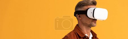 Photo for Panoramic shot of man in virtual reality headset isolated on orange - Royalty Free Image