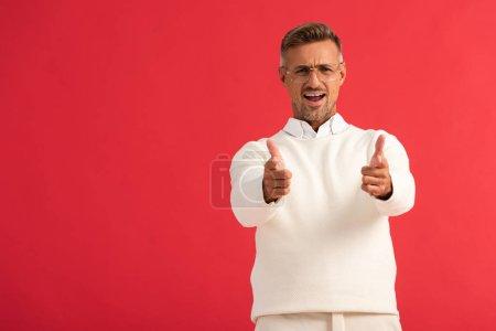 Aufgeregter Mann mit Brille zeigt mit roten Fingern