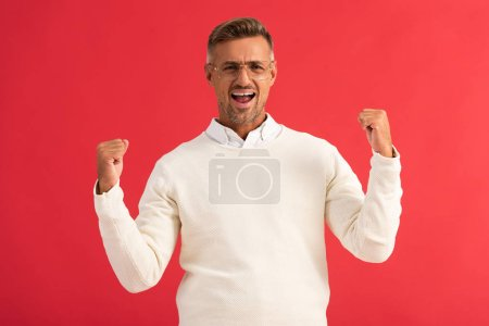 Photo for Excited man in glasses celebrating triumph isolated on red - Royalty Free Image