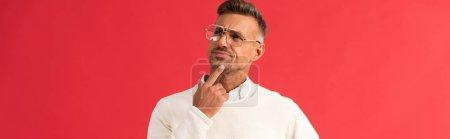 Photo pour Plan panoramique de l'homme cher dans des lunettes touchant le visage isolé sur rouge - image libre de droit