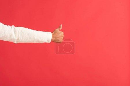 Photo pour Vue recadrée de l'homme montrant pouce vers le haut isolé sur rouge - image libre de droit