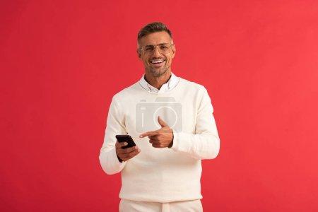 Photo pour Homme heureux dans des lunettes pointant du doigt le smartphone isolé sur rouge - image libre de droit
