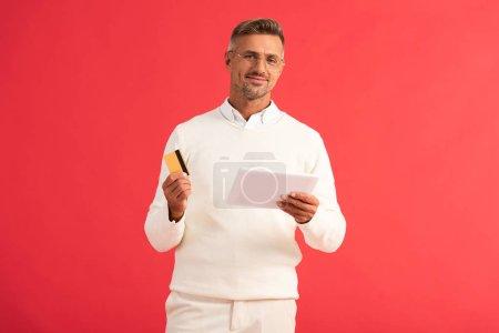 Photo pour Homme heureux tenant tablette numérique et carte de crédit isolé sur rouge - image libre de droit