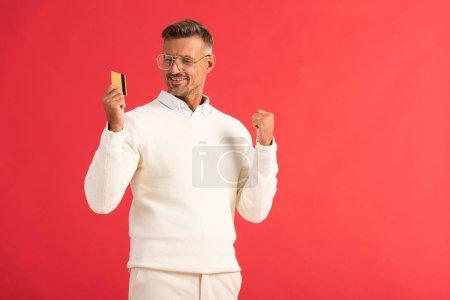 Photo pour Homme heureux dans des lunettes tenant carte de crédit isolé sur rouge - image libre de droit