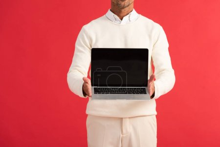 cropped view of man holding laptop with blank screen isolated on red