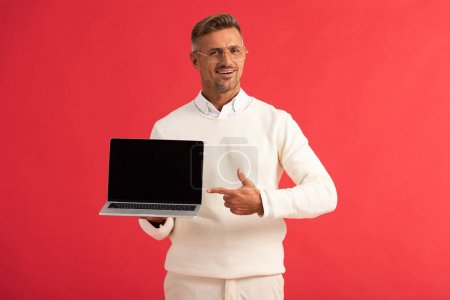 happy man in glasses pointing with finger at laptop with blank screen isolated on red