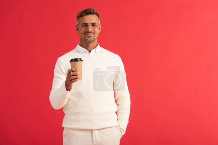 Photo pour Homme heureux en lunettes tenant une tasse de papier isolée sur du rouge - image libre de droit