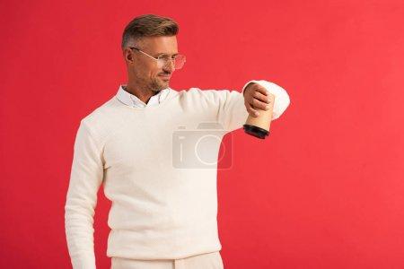 Photo pour Bel homme dans des lunettes tenant tasse en papier à l'envers isolé sur rouge - image libre de droit