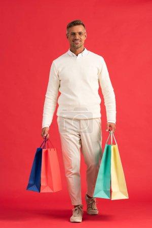 Photo pour Homme gai dans des lunettes tenant des sacs à provisions colorés sur rouge - image libre de droit