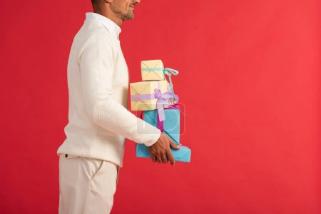 Photo for Cropped view of smiling man holding gift boxes isolated on red - Royalty Free Image