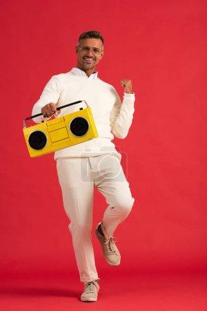 Photo pour Positif homme en lunettes tenant une boombox jaune sur rouge - image libre de droit