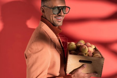 Photo for Smiling man in blazer and sunglasses holding box with sweet peaches on red with shadows - Royalty Free Image