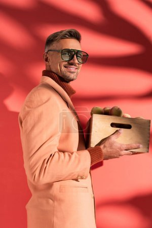happy man in blazer and sunglasses holding box with sweet peaches on red with shadows