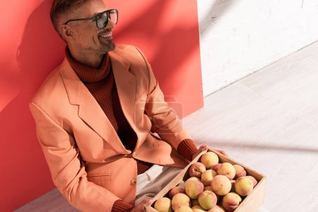 cheerful man in blazer and sunglasses sitting with sweet peaches in box on red and white with shadows