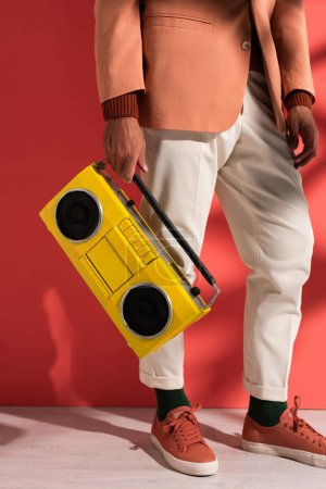 cropped view of stylish man holding boombox on red with shadows