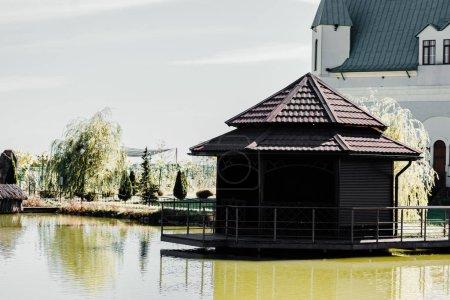 Photo pour Lumière du soleil sur le toit des bâtiments près de l'étang et des arbres dans le zoo - image libre de droit