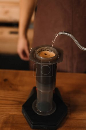 cropped view of barista pouring water from kettle in aeropress while preparing coffee