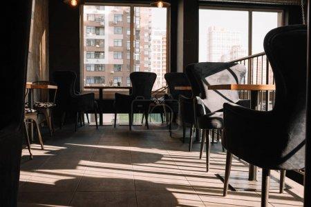 Photo pour Balcon avec tables et chaises dans un café moderne au soleil - image libre de droit