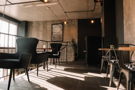 Photo for Balcony with tables and chairs in modern loft coffee house in sunshine - Royalty Free Image