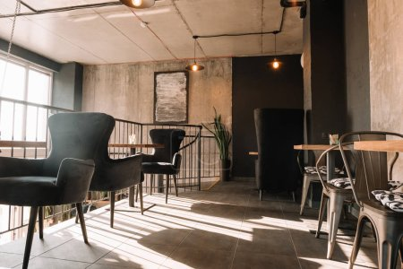 Photo for Balcony with tables and chairs in modern loft coffee house in sunlight - Royalty Free Image