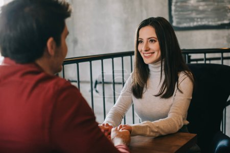Photo pour Une jeune femme souriante regardant son petit ami et lui tenant les mains sur le balcon d'un café - image libre de droit