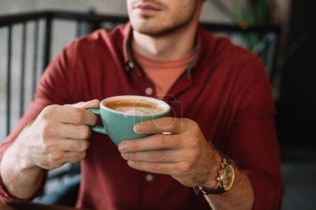Photo pour Vue en coupe d'un jeune homme avec une tasse de savoureux cappuccino dans un café - image libre de droit