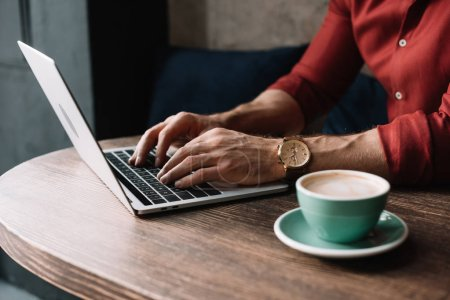 Photo pour Vue recadrée de jeune pigiste travaillant sur ordinateur portable et près de tasse de cappuccino dans un café - image libre de droit