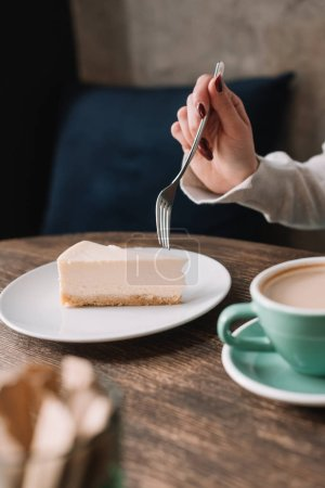 Photo for Cropped view of woman eating cheesecake with fork and drinking coffee in cafe - Royalty Free Image