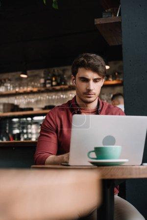 Photo pour Freelance dans les écouteurs sans fil en utilisant un ordinateur portable dans le café - image libre de droit