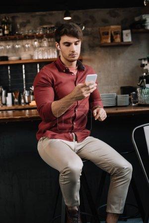 Photo pour Bel homme assis près du comptoir de bar dans les écouteurs sans fil en utilisant un smartphone - image libre de droit