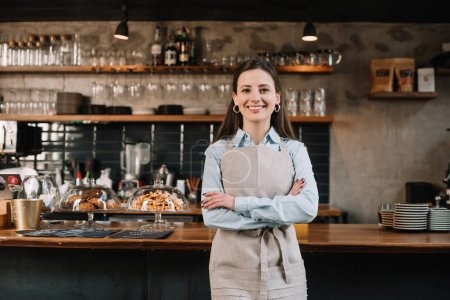 Photo for Smiling barista in apron standing with crossed arms near bar counter - Royalty Free Image
