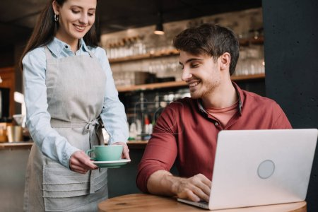 Photo for Smiling waitress serving coffee to freelancer with laptop - Royalty Free Image
