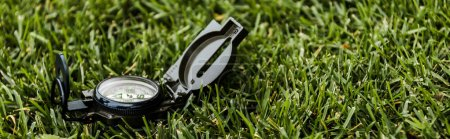 Photo for Panoramic shot of black retro compass on green grass - Royalty Free Image