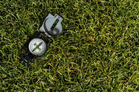 Photo for Top view of retro compass on green grass - Royalty Free Image