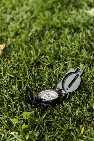 Photo pour Foyer sélectif de boussole noire et vintage sur herbe verte - image libre de droit